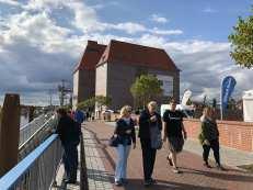 Menschen an der Promenade vor der alten Ölmühle